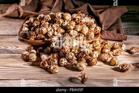 Caramel popcorn in a wooden bowl on a wooden background. Low key lighting. Selective focus. Close-up - Stock Photo