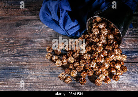 Caramel popcorn on a wooden background. Low key lighting. Selective focus. Close-up. Top view - Stock Photo
