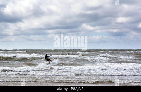 Kitesurfer is riding the waves of Baltic sea near Venspils beach under the cloudy sky. Fun in the sea. Extreme sport kitesurfing. - Stock Photo