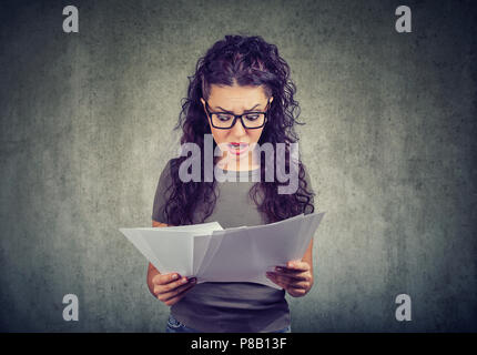 Young brunette in glasses exploring papers from bank with list of bills and fees looking stressed on gray background - Stock Photo