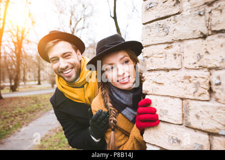 cheerful young couple in autumn outfit looking at corner - Stock Photo