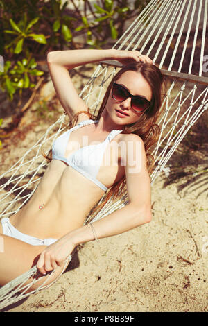 young woman in bikini lying in hammock on beach - Stock Photo