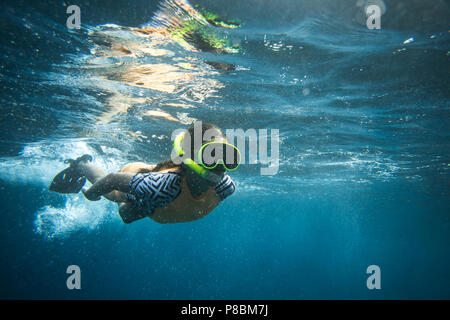 underwater photo of woman in diving mask and snorkel diving alone in ocean - Stock Photo
