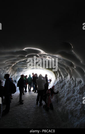 People waiting at this icy place for the arrival of their family members and friends, who are climbing the Aiguille-du-Midi in the Mont Blanc massif - Stock Photo