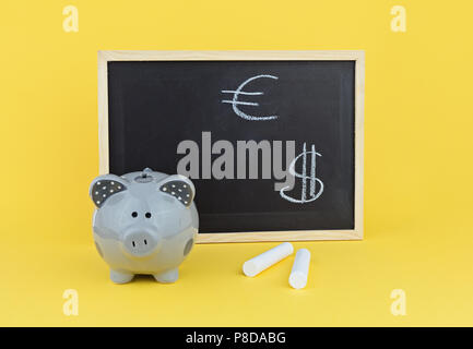 Funny pig piggy bank on background of chalk board with signs of the Euro and Dollar. Concept of studying exchange rate statistics - Stock Photo