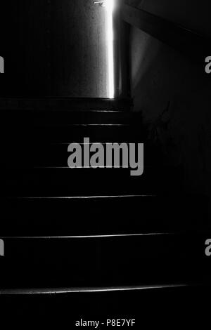 Dark image in black and white of stairs leading up from cellar to a door ajar. - Stock Photo