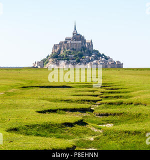 View of the Mont Saint-Michel tidal island in Brittany, France, with the dry bed of a stream snaking in the salt meadow in the foreground. - Stock Photo