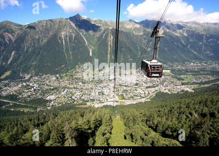 Cable car heading for the peak of the Aiguille-du-Midi in the Mont Blanc massif - Chamonix, France, in the background - Stock Photo