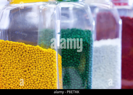 Granules of different shapes for the production of multi-colored plastic parts for industry - Stock Photo