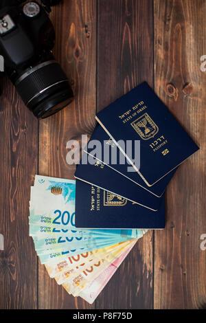 Stack of israeli money bills of 200 shekel and israeli passport. - Stock Photo