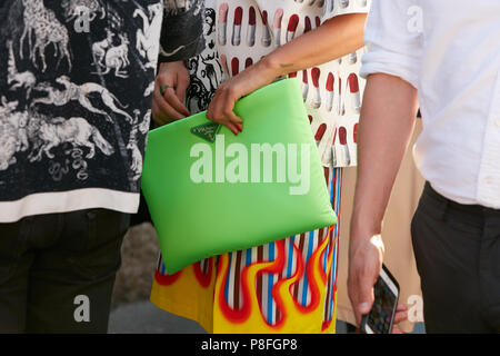 MILAN - JUNE 17: Woman with green Prada bag and skirt with flames before Prada fashion show, Milan Fashion Week street style on June 17, 2018 in Milan - Stock Photo