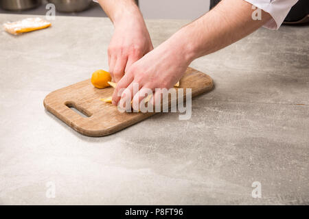 Male hands making homemade dumplings pastry tortellini or ravioli. Model for home made pasta filled with seafood - Stock Photo