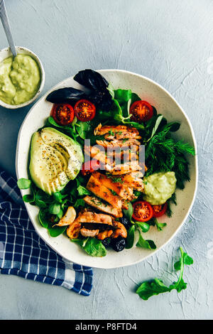 Keto chicken salad with herbs like arugula, basil and fresh dill, avocado, olives, seeds and cherry tomatoes in a ceramic salad bowl photographed from - Stock Photo