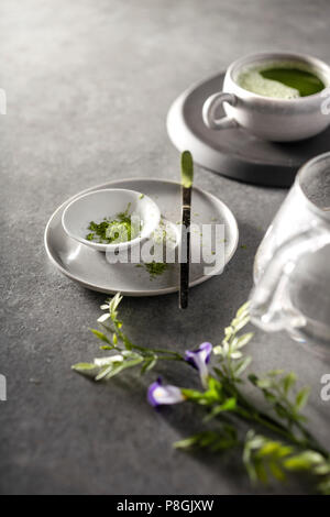 Matcha powder and matcha tea being prepared on a gray concrete countertop in the morning light. - Stock Photo