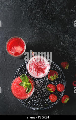 Three different red fruit berry watermelon, strawberry, raspberry, pomegranate cocktails or smoothies in glasses with crushed ice, fresh mint, ingredi - Stock Photo