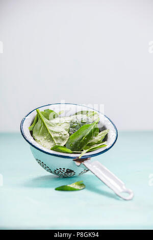 Spinach. Fresh organic spinach leaves in metal colander. Diet, dieting concept. Vegan food, healthy eating. Rustic style - Stock Photo
