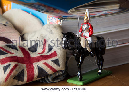 Cavalry guard with England flag and travels guide behind on the wooden table - Stock Photo