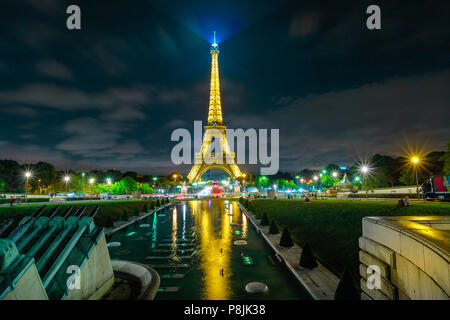 Paris, France - July 2, 2017: Eiffel Tower reflect in the pool of fountains during lights show in the evening. Jardins du Trocadero with night lighting. Paris skyline on the background. - Stock Photo
