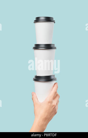 Crop hand holding stack of paper cups - Stock Photo