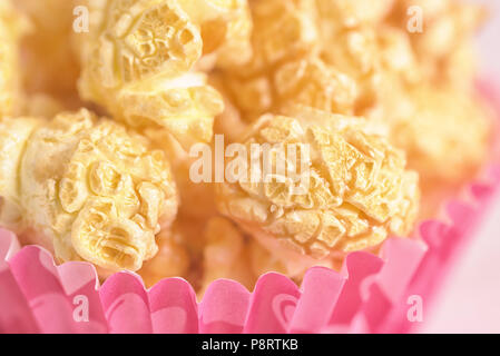 Popcorn on the table. Cup with popcorn on pink background - Stock Photo