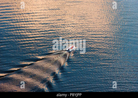 Aerial view of a small boat on wide blue water surface in evening sun. Diagonal composition suitable background. - Stock Photo