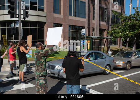 Los Angeles, USA. 13th July, 2018 - Protesters blocking road while protesting ICE and private contractor The GEO Group in Los Angeles, USA. Credit: Aydin Palabiyikoglu Credit: Aydin Palabiyikoglu/Alamy Live News - Stock Photo
