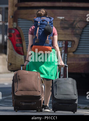 Frankfurt, Germany. 13th July, 2018. A woman pulling her suitcases to a waiting bus. There are constant chaotic transport scences at the bus parking area on the south side of the central station. The new distant bus station should be finished at the start of 2019. Credit: Boris Roessler/dpa/Alamy Live News - Stock Photo