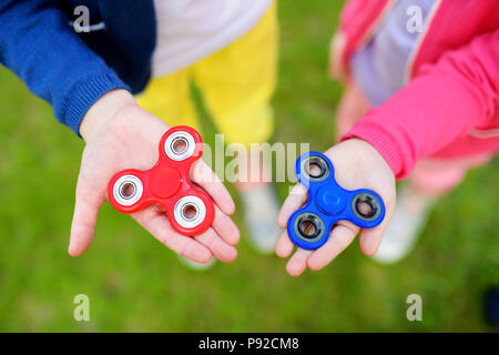 Two school children playing with colorful fidget spinners on the playground. Popular stress-relieving toy for school kids and adults. - Stock Photo
