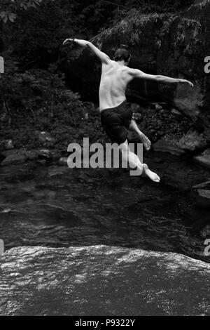 A tourist jumps into a pristine creek near Kuraburi, a town on the North Andaman Coast - THAILAND - Stock Photo