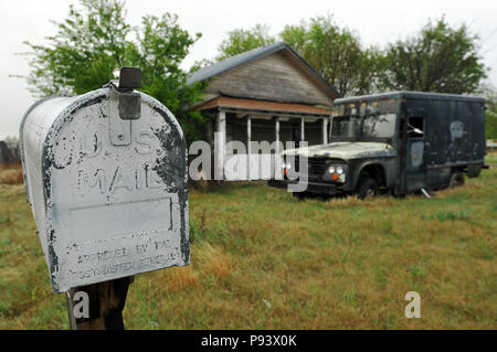A weathered mailbox stands near an abandoned vehicle and home on a rural property in the Route 66 town of Texola, Oklahoma. - Stock Photo