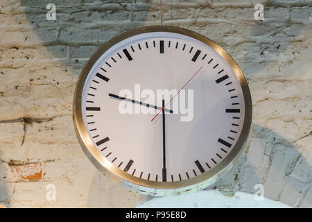 Big old clock in an old factory in front of a window - Stock Photo