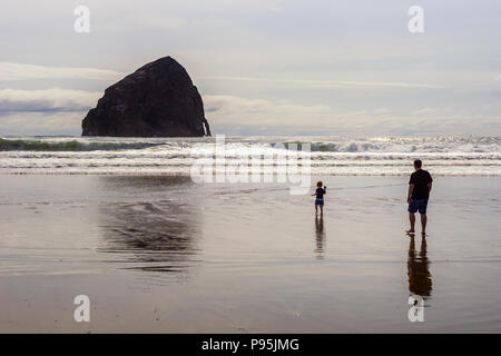 Father with his child walking on the beach with the Haystack Rock in the background, Cape Kiwanda State Natural Area, Pacific City, Oregon Coast, USA. - Stock Photo