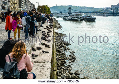 Tourists visit and take photos at The Shoes on the Danube Bank, a memorial in Budapest, Hungary with the Chain Bridge and boats in the background - Stock Photo