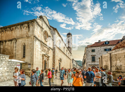 Crowds of tourists walk the main street or stradun next to St Saviour Church in the ancient walled city of Dubrovnik, Croatia - Stock Photo