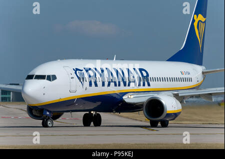 A Ryanair Boeing 737-8AS taxis along the runway at Manchester Airport whilst preparing to take off. - Stock Photo