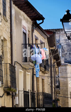 Detail of an iron balcony with clothes hanging to dry in a stone house typical of the villages of northern Spain - Stock Photo