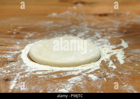 Pizza dough. Basis for baking pizza on a wooden table, close-up - Stock Photo