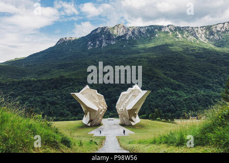 two tourists are dwarfed by the big white Tjentište spomenik (Yugoslav war memorial monument) in the Sutjeska National Park, Bosnia and Herzegovina - Stock Photo