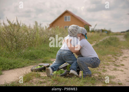 two brothers playiung outside and having a tumble - Stock Photo