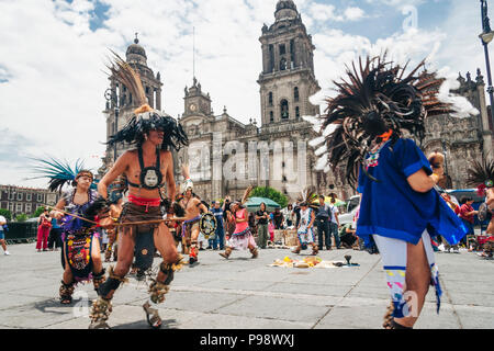 Mexico City, Mexico : Aztec people dancing opposite the Cathedral at the Zócalo square (Plaza de la Constitución) in the historic center of  Mexico Ci - Stock Photo