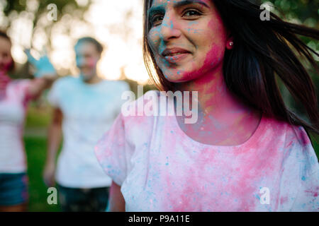 Young woman face smeared with colors. Girl playing with friends at back during festival of colors. Playing holi with friends. - Stock Photo