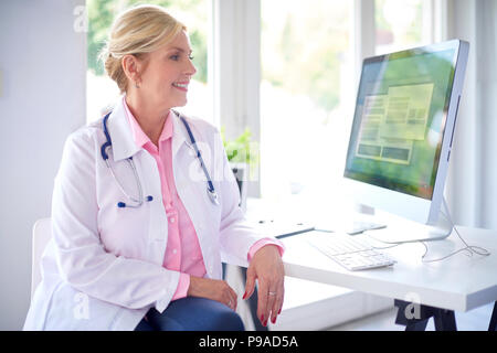 Beautiful smiling female doctor sitting in front of her computer at the doctor's office and working. - Stock Photo