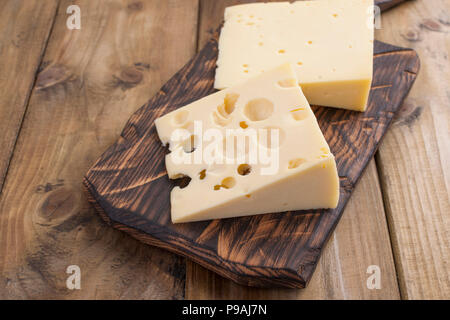 Dutch cheese with holes on a wooden old board. Vintage photo. Dairy. Free space for text. Copy space - Stock Photo