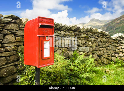 Rural red Royal Mail post letter box and dry stone wall in a remote part of the Lake District National Park, Cumbria, rural England, UK - Stock Photo