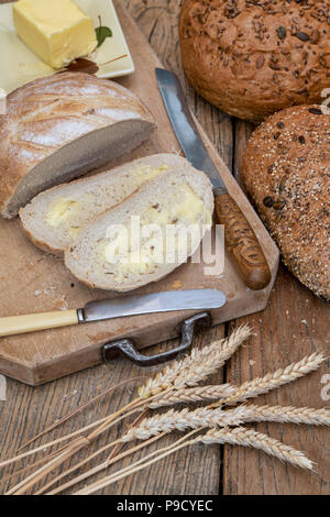 Sliced White bread with seeded loaves on a bread board with wheat and a bread knife. UK - Stock Photo