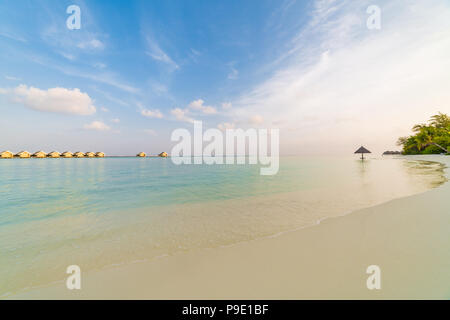Amazing Maldives scenery, water villas and beach umbrella with palm trees. Tranquil sunset landscape in tropical beach. Luxury vacation destination - Stock Photo