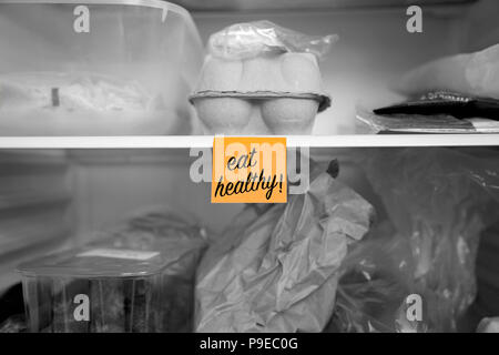 Eat healthy written on a post it note stuck on a fridge shelf with food.  Abstract with selective colour - Stock Photo