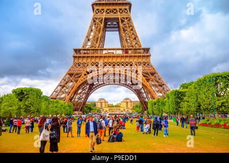 Paris, France - July 1, 2017: many people on Champ de Mars looking the Tour Eiffel, icon and symbol of Paris. Cloudy sky in a summer day. Europe travel concept. - Stock Photo