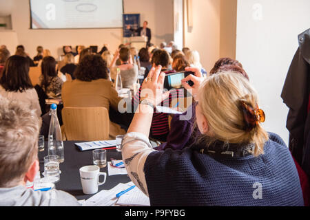 Blonde white middle-aged woman holds up her smartphone to take a photo of a powerpoint presentation at a conference with lots of people in the room - Stock Photo