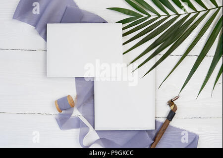 White blank greeting card ribbon on a background of blue fabric with palm leaf and calligraphic pen on a white background. Mockup with envelope and blank card. Flat lay. Top view - Stock Photo